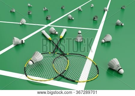 Badminton Rackets With Shuttlecocks. Black Rackets With Yellow Stripes On The Green Floor In A Badmi