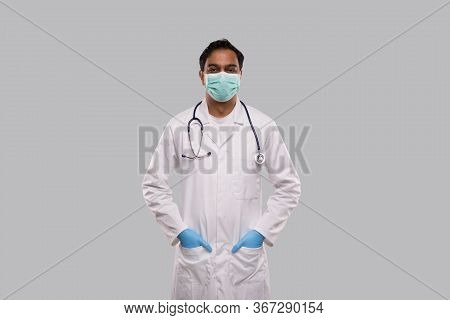 Male Doctor Wearing Medical Mask And Gloves Standing Isolated. Indian Man Doctor Medical Workwear. M