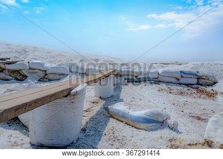 Brine Salt Farm With Blue Sky And White Clouds. Pile Of Organic Sea Salt Near Warehouse. Raw Materia