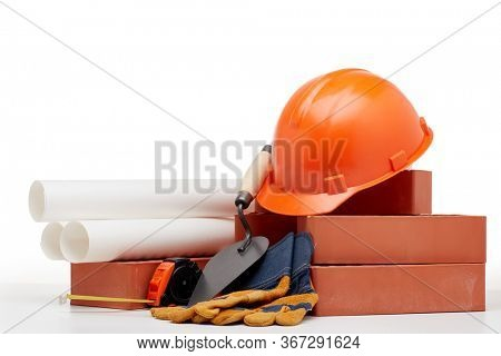 Construction concept. Stack of new bricks with masonry trowel, architectural blueprints, tape measure, construction orange hard hat and protective  gloves on white background with copy space.