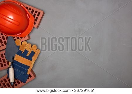 Construction concept. Stack of new bricks with masonry trowel, construction orange hard hat and protective  gloves on gray concrete background. Top view with copy space.