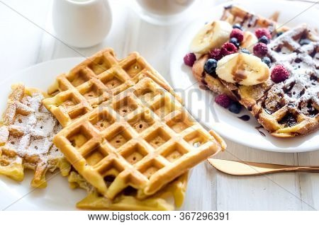 White Plate Of Belgian Waffles With Sugar Powder, Frozen Berries, Banana And Caramel Sauce With Cup