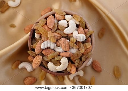 Delicious And Healthy Mixed Dried Fruit, Nuts And Seeds In A Wooden Bowl On Golden Silky Background.