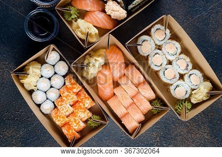 Tasty Sushi Rolls In Disposable Kraft Paper Boxes, Sauces On Dark Table. Concept Delivery Service Ja