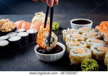 Tasty Sushi Rolls Set On Stone Plate With Sauces, Chopsticks, Ginger And Wasabi On Dark Table. Sushi