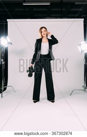 Beautiful Model In Formal Wear Holding Digital Camera Near Floodlights In Photo Studio