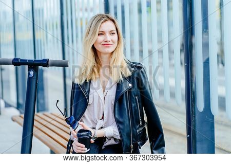 Young Millennial Woman Rides A Cool Electric Scooter Past A Bus Stop On A Sunny Autumn Day. Smiling