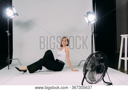 Side View Of Young Woman Sitting On Floor Near Floodlights And Electric Fan In Photo Studio