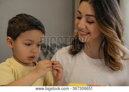 Cheerful Woman Looking At Son Sculpting Plasticine Figure