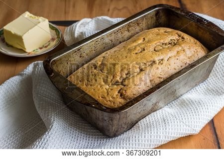 Banana Loaf In Loaf Tin With Butter On Kitchen Table