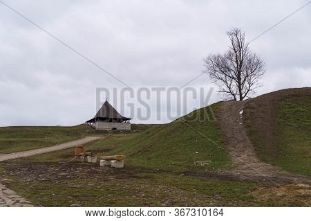 Landscape: Entrance Gates To The Khotyn Fortress, A Tree On A Hill And Benches In Winter