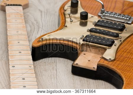 Electric Guitar Repair. Close-up Of Neck Removed From Body For Refinishing. Preparation For Fret Dre