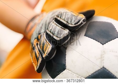 Soccer Background Detail Image. Close Up On Football Ball And Sports Goalie Gloves. Footballer Goalk