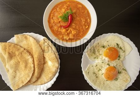 Famous Traditional Arabic Breakfast - Peeled Fava Beans With Chili Pepper In White Bowl, Pita Bread