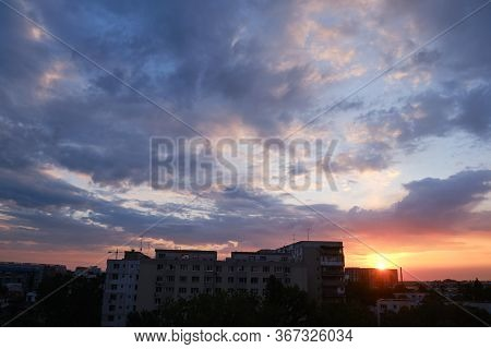 Urban Sunrise With Purple And Orange Clouds In The Sky, After A Storm, In Bucharest, Romania.