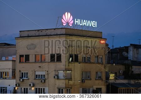 Huawei Logo On Top Of A Building With Dilapidated Exterior In Eastern Europe, At Sunset. Bucharest,