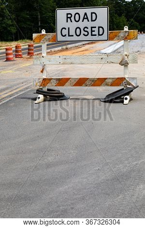 Road Closed Sign On A Battered Traffic Barricade, Safety Barrels And Roadway Construction, Creative