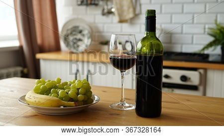 Close Up Of Open Bottle Of Wine And Glass Of Wine With Fruits On Plate On Table In Kitchen. Concept