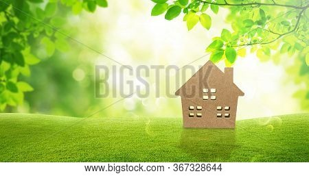 Housing And Green Ecology Concept : Wooden Home On Green Grass With Green Natural And Sunlight In Ba
