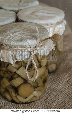 Canned Forest Mushrooms In A Glass Jar On Burlap. Closeup Of Pickled Mushrooms In Closed Glass Jars.