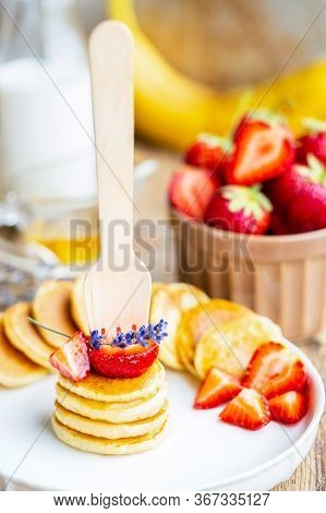 Skewers Of Mini Pancakes With Strawberries. Canapes From Mini Pancakes. Oatmeal Banana Fritters With