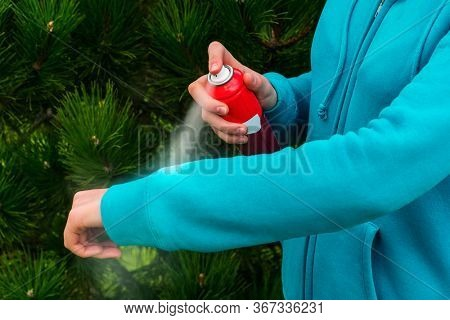 Woman applying mosquito repellent on hand during hike in nature