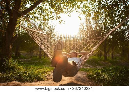 Blurry And Defocus Relaxing In Hammock In Sunny Day. Man Rest In Garden. Summer Vibes In Forest