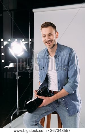 Smiling Photographer Holding Digital Camera Near Floodlight In Photo Studio