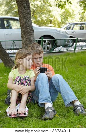 Boy looks frowning at the phone screen, his younger sister sits next to him on grass and looks over his arm