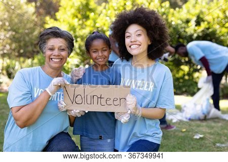 Mixed race girl spending time outside with her family, holding a volunteer sign with her mother and grandmother, looking at the camera and smiling, all wearing blue volunteer t shirts, on a sunny day