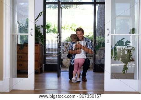 Caucasian girl enjoying her time at home, standing in a hallway, greeting her father who is kneeling, embracing and smiling