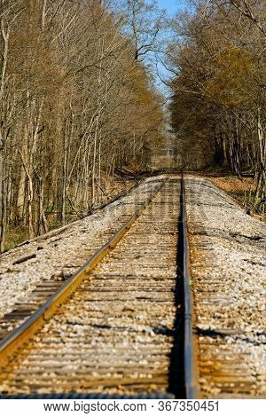 An Old Railroad Track Heads Into A Wooded Area At The Very Beginning Of Spring In Northeast Ohio