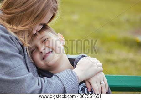 A Young Happy Boy Hugging His Mom. Mom Hugs Her Son. Family In The Park