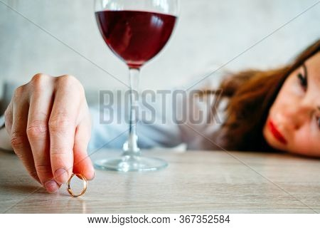 The Girl Is Sad Because Of The Breakup And Holds A Wedding Ring Next To A Glass Of Wine. Close Up.