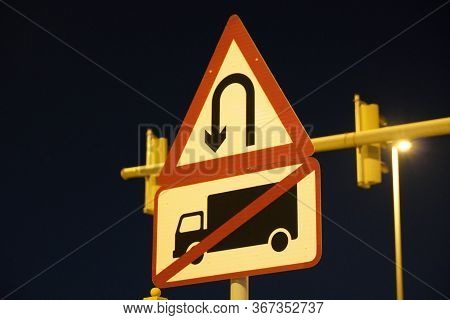 U-turn Signs On The Street At Night Is A Grain Film Image. U Turn Sign After Sunset. View Of Dark, B