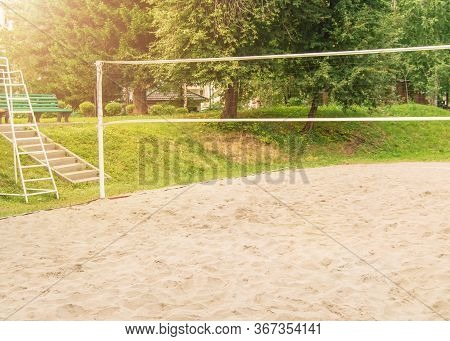 An Empty Playground With Sand And A Volleyball Net For Playing Beach Volleyball, Sunlight On A Summe