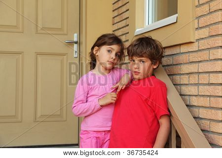 Brother and sister stand near door of cottage and look into camera.