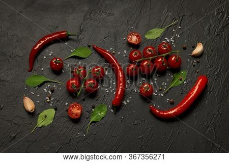 Hot Chili Peppers Pods, Cherry Tomatoes, Garlic, Rucola Leaves And On A Black Background.