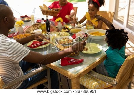 Side view of a multi-ethnic, multi-generation family serving food and sitting at a table for a meal together outside on a patio in the sun, the African American father serving his young son some food