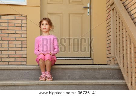Little serious girl in pink suit sits on stairs near door and looks into distance.