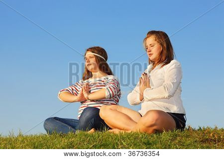 Two young girls meditate and reflect at green grass at background of blue sky.