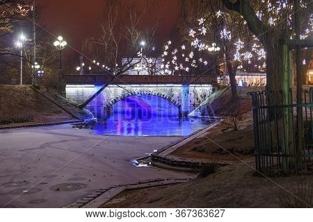 Night Winter View Of The Alexander Bridge In Bastion Hill Town Park In Riga (latvia). The Bridge Was