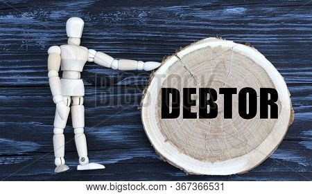 Debtor Word On A Wooden Circle On A Dark Background With A Male Figurine. Business Concept