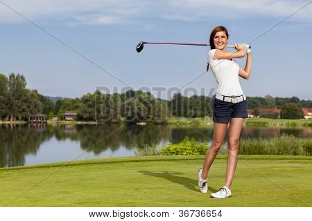 Girl golf player teeing-off with driver from tee-box, front view.