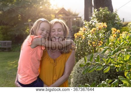 Front view of a Caucasian woman and her granddaughter in the garden on a sunny day, the woman carrying her granddaughter who is embracing her, both are smiling with their eyes closed