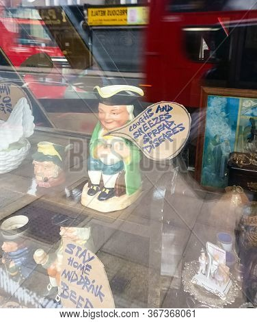 London, United Kingdom - March 30, 2020: Charity Shop Window Displaying Artsy Handmade Craft Statute