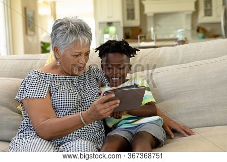 Front view of a senior mixed race woman at home in the living room, sitting on the couch with her arm around her African American grandson, smiling and looking at a tablet computer together