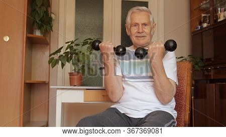 Senior Elderly Caucasian Man In Sportswear Sitting On Chair In Living Room, Doing Weight Lifting Dum