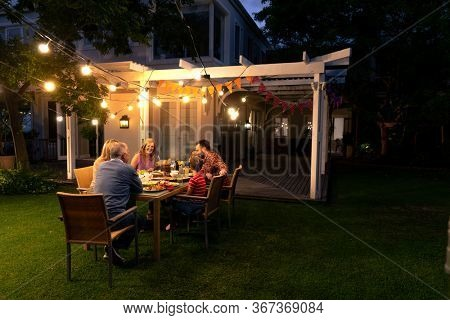 Side view of a multi-generation Caucasian family sitting in the garden outside their house at a dinner table in the evening for a celebration meal together, talking and eating