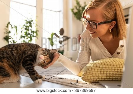 Smiling Woman Freelancer In Glasses Lies On The Carpet In Living Room At Home, Stroking And Plays Wi